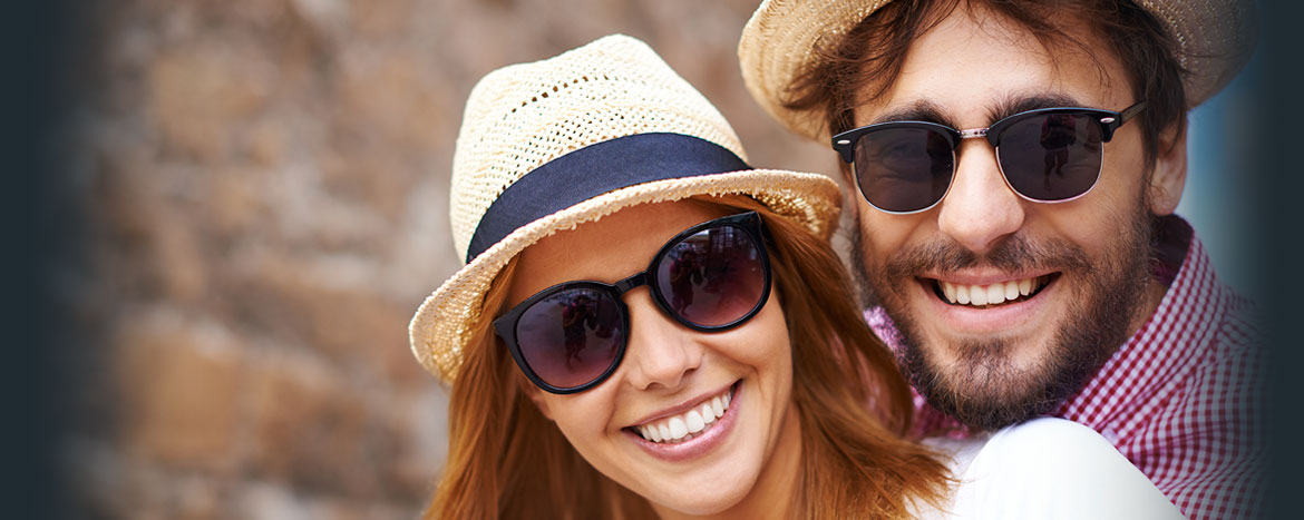a young couple wearing sunglasses and nice hats